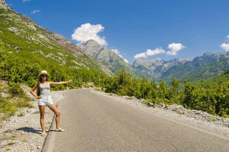 Young woman hitchhiking along empty road. Young attractive woman hitchhiking along empty road stock photos