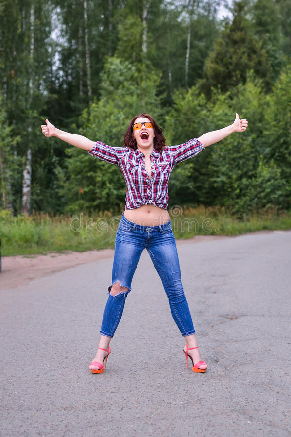 Young woman hitchhiking gesture at countryside. Young woman persistently hitchhiking gesture at countryside royalty free stock photography