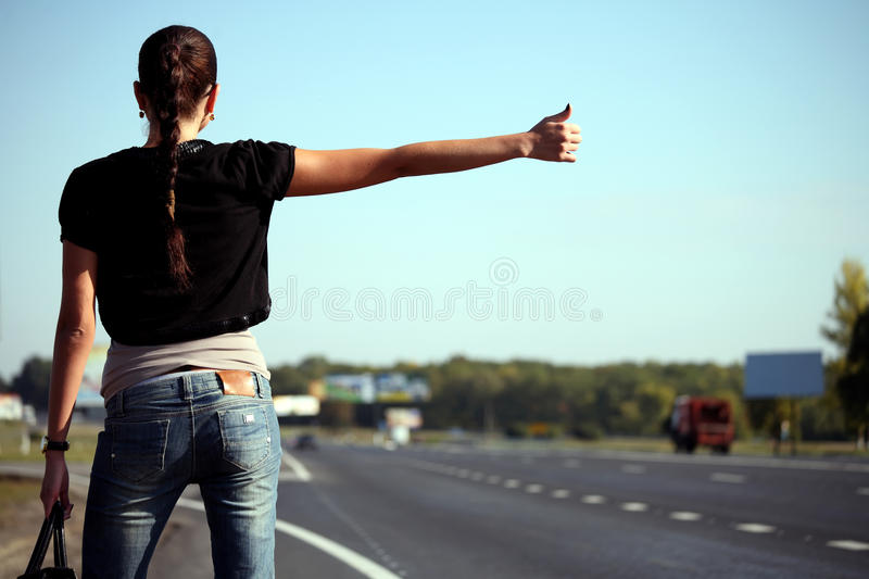 Young woman hitchhiking on the road. Back view stock photo