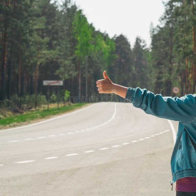 Woman   hitchhiking on the road square image. Young woman   hitchhiking on the road square image stock image