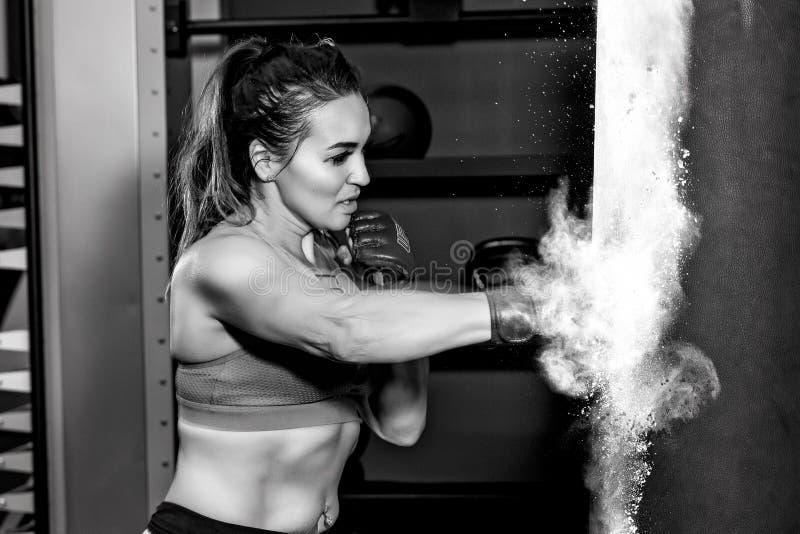 Young woman hitting punching bag royalty free stock photography