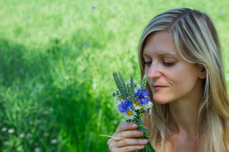 Young woman hold meadow flower made from cornflower, snow lady, forget me not and wheat stock image
