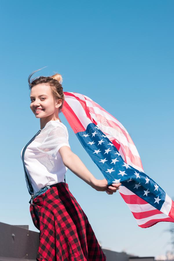 young woman holding american flag against blue sky independence stock photography