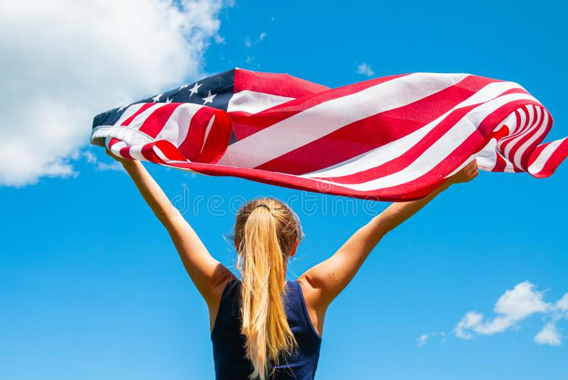 Young woman holding American flag on blue sky background.  4th of July. Young woman holding American flag on blue sky background. United States celebrate 4th of royalty free stock photography