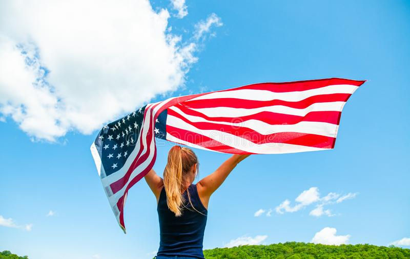 Young woman holding American flag on blue sky background. United States celebrate 4th of July. Independence Day. Young woman holding American flag on blue sky stock images