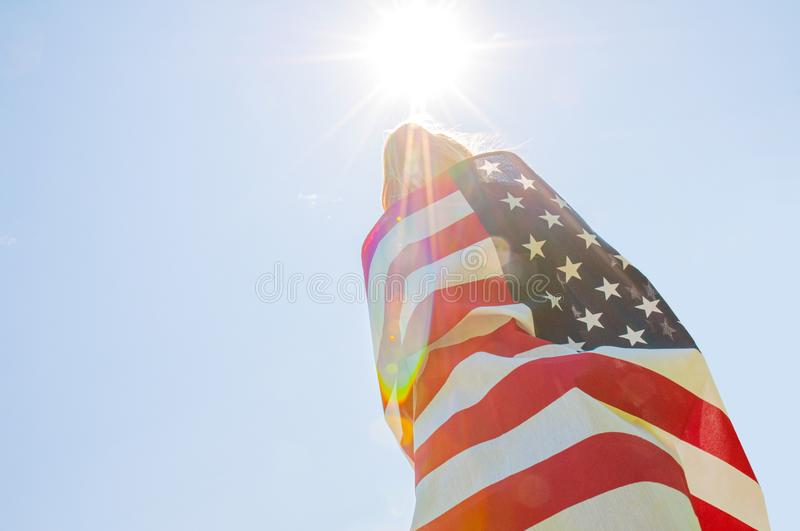 Woman holding American flag on blue sky background. United States celebrate 4th of July. Young woman holding American flag on blue sky background. United States royalty free stock images