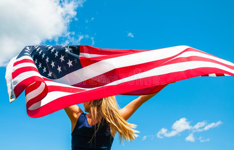 Woman holding American flag on blue sky background. United States celebrate 4th of July. Young woman holding American flag on blue sky background. United States royalty free stock image