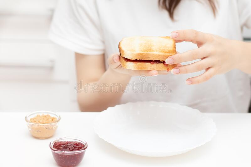 A young woman is holding an American sandwich with jam and peanut butter, preparing to eat it for breakfast in the morning at home royalty free stock photo
