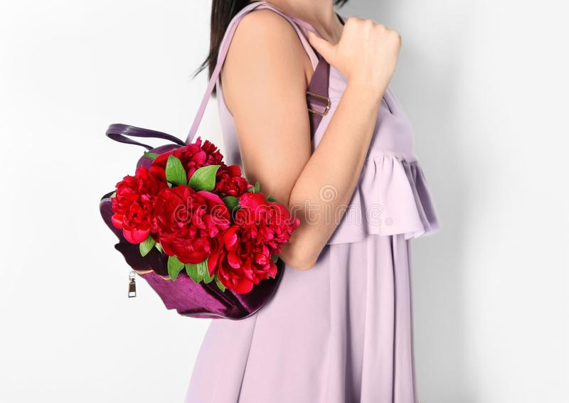 Young woman holding backpack with beautiful peonies on light background royalty free stock photos