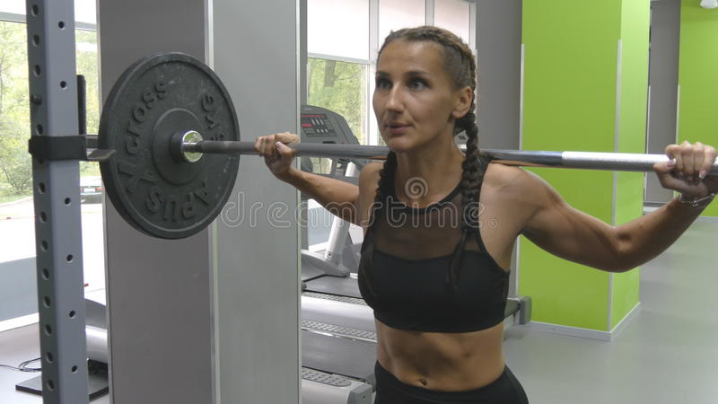 Young woman holding a barbell with heavy weights on her shoulders as she squats. Strong girl training in the gym stock images