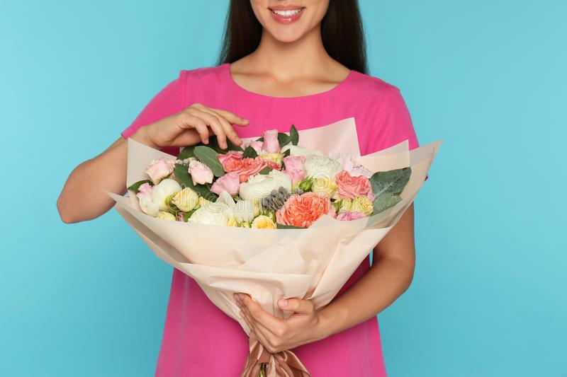 Young woman holding beautiful flower bouquet on light blue background, stock images