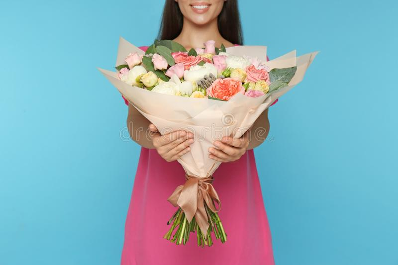 Young woman holding beautiful flower bouquet on light blue background royalty free stock photography