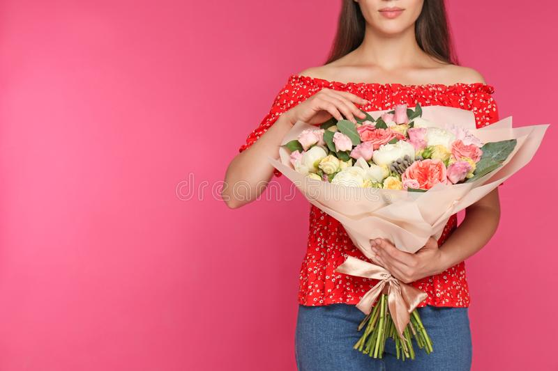 Young woman holding beautiful flower bouquet on pink background, closeup stock photography