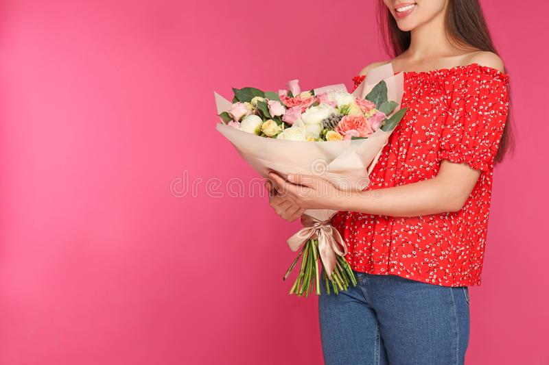 Young woman holding beautiful flower bouquet on pink background. Space for text stock photo