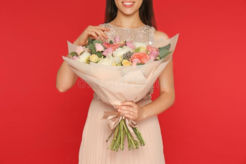Young woman holding beautiful flower  on red background, closeup royalty free stock photos