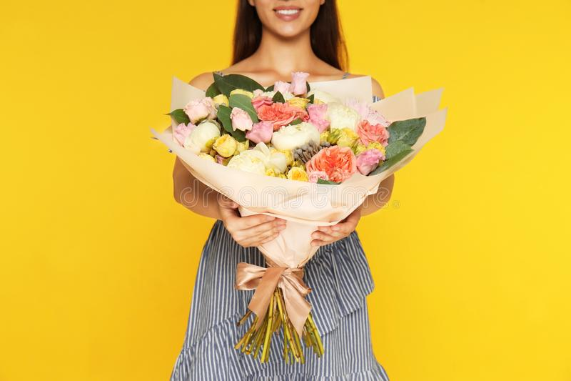 Young woman holding  flower bouquet on yellow background, closeup stock photos