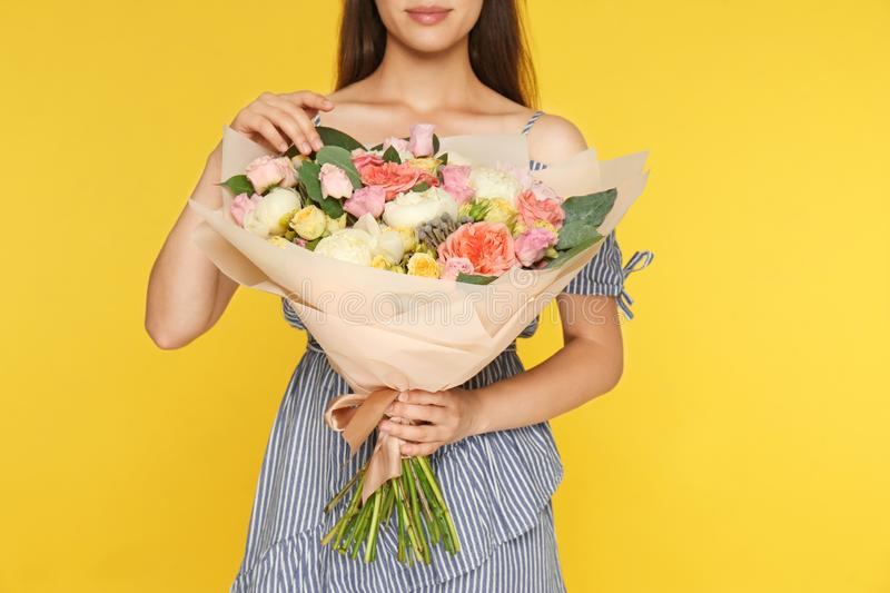 Young woman holding beautiful flower bouquet on yellow background stock photography