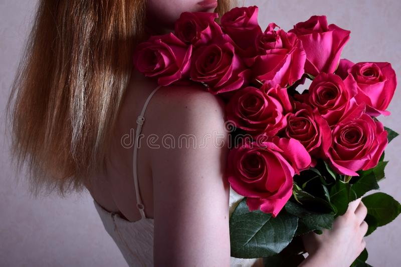 Young woman is holding a big bouquet of pink roses. Young woman wearing a strap shoulderless dress is holding a big bouquet of pink roses royalty free stock photos