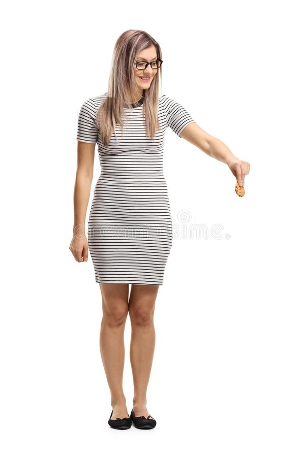 Young woman holding a biscuit and looking downwards royalty free stock photos
