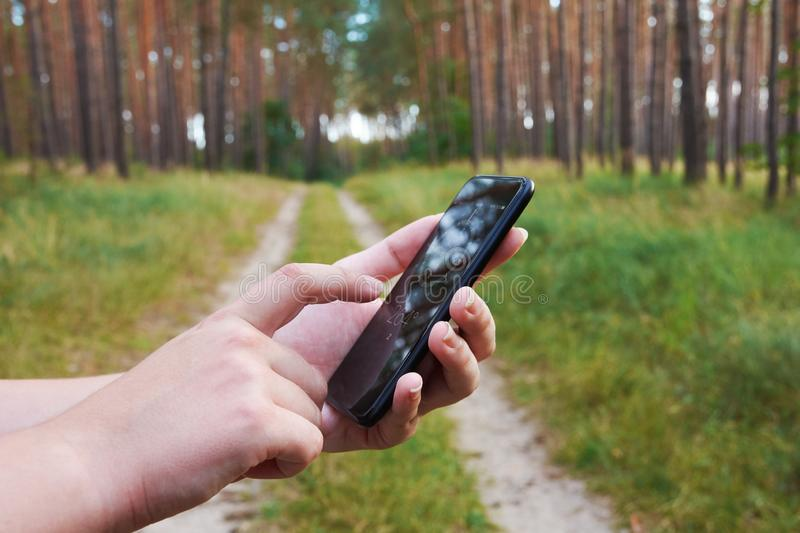 Young woman holding a black cell phone with a compass on the screen and touching his finger. With a blurred forest and a path. Young woman holding a black cell stock photos