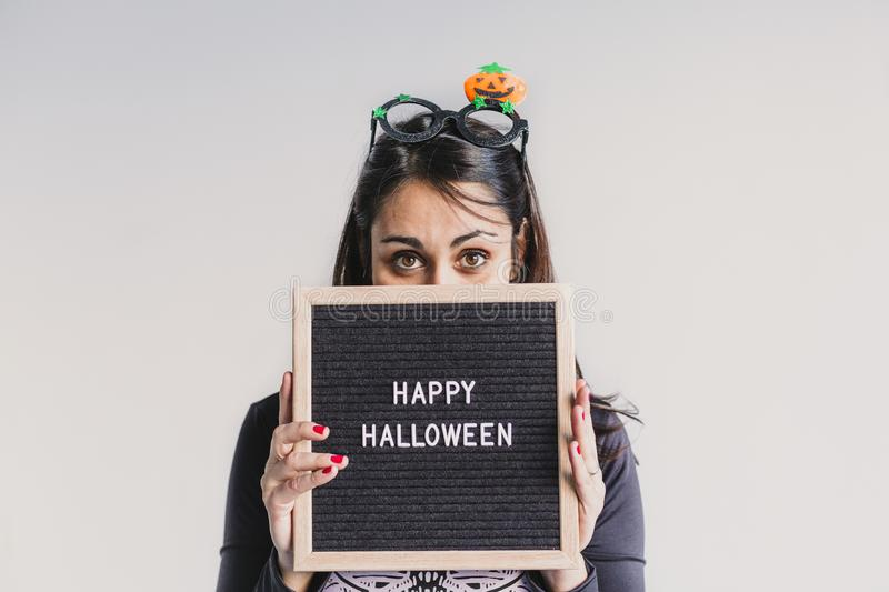 Young woman holding a black vintage letter board with happy halloween sign. White background. LIfestyle indoors. Skeleton costume. Blackboard, candies royalty free stock images