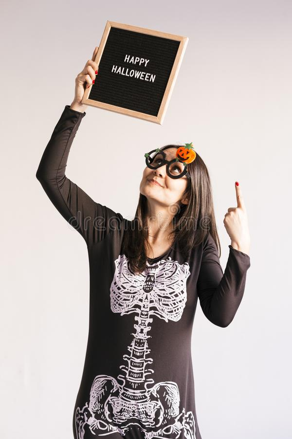 Young woman holding a black vintage letter board with happy halloween sign. White background. LIfestyle indoors. Skeleton costume. Blackboard, candies royalty free stock photos