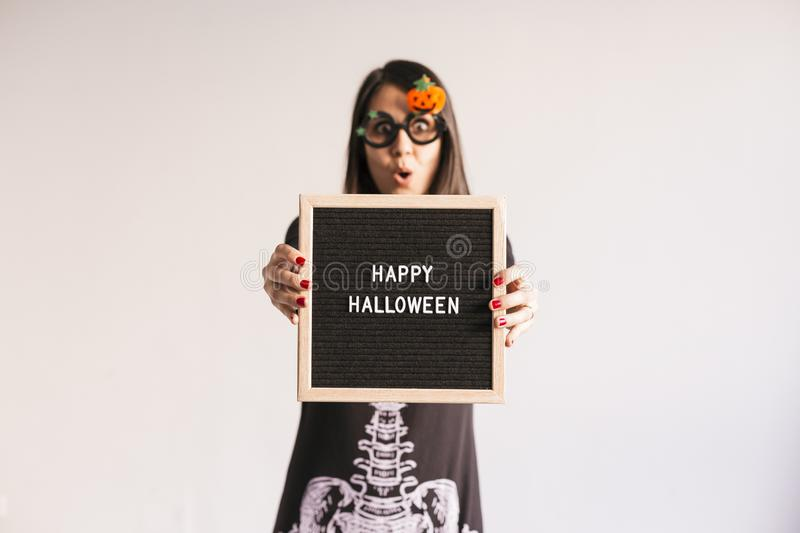 Young woman holding a black vintage letter board with happy halloween sign. White background. LIfestyle indoors. Skeleton costume. Blackboard, candies stock images