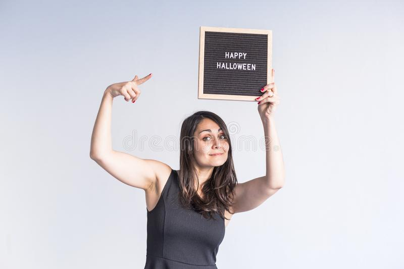 Young woman holding a black vintage letter board with happy halloween sign. White background. LIfestyle indoors. Blackboard, candies, caucasian, smile stock images