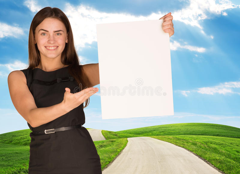 Young woman holding blank poster with nature on. Background. Place for constraction royalty free stock image