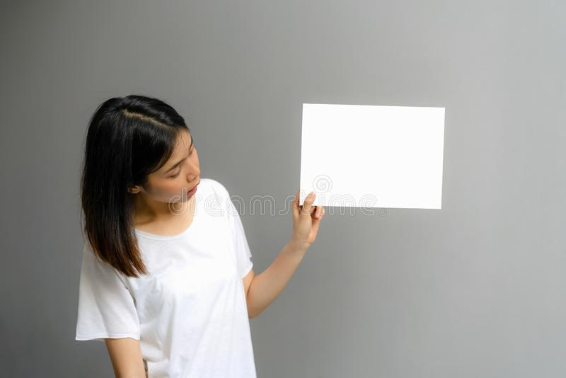 Young woman holding a blank poster for text on a white background. royalty free stock photo