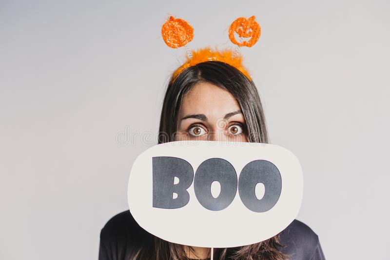 Young woman holding a boo sign. Wearing a black and white skeleton costume. Halloween concept. Indoors. Lifestyle. Holiday, pumpkin, fall, spooky, face stock photography