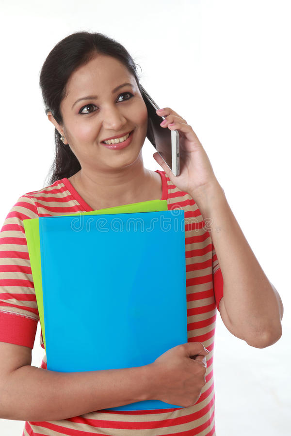 Young woman holding books and talking on mobile phone stock photo