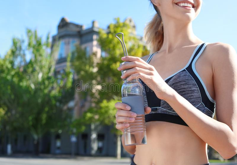 Young woman holding bottle with clean water on street. Space for text stock photography