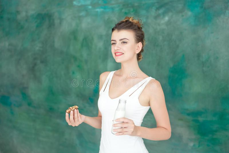Young woman holding a bottle of milk wearing in white singlet indoor stock photos