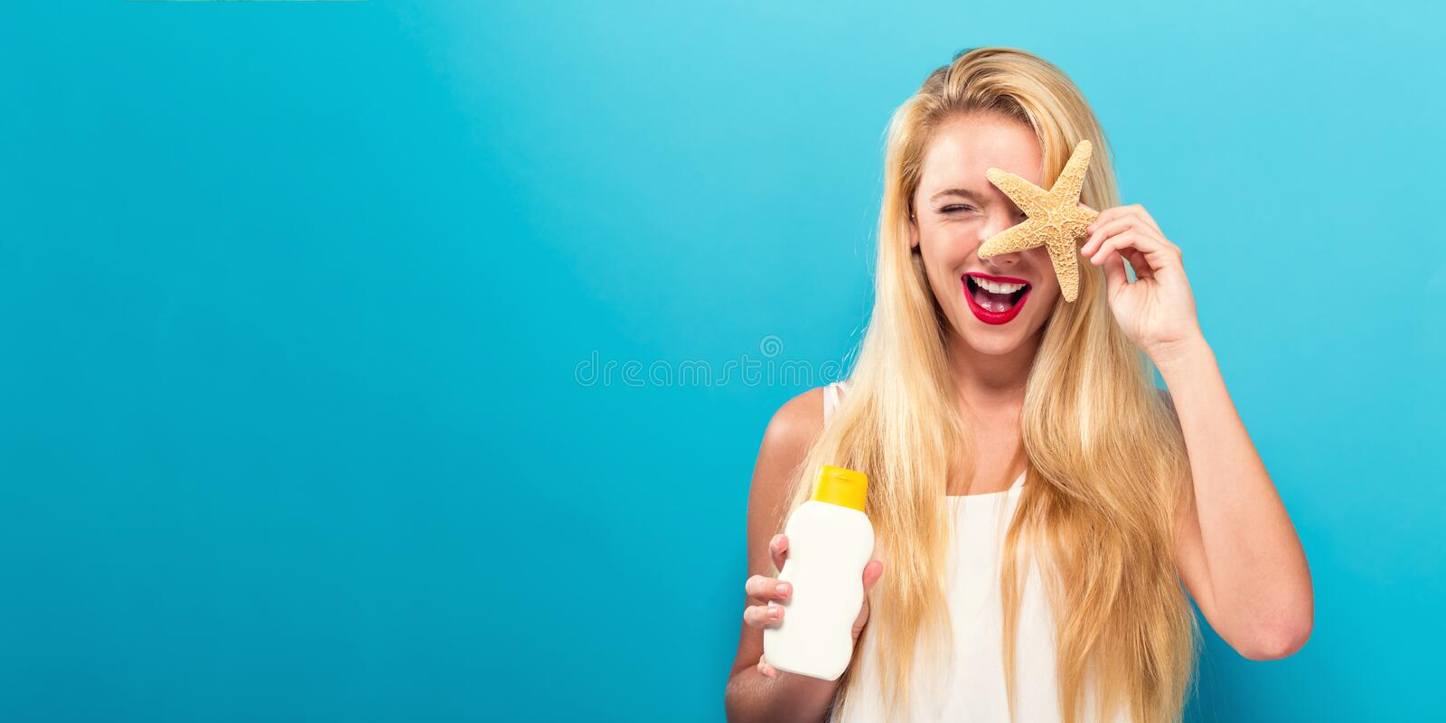 Young woman holding a bottle of sunblock royalty free stock photos