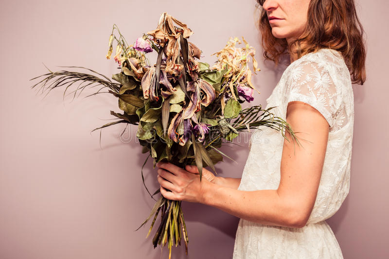 Young woman holding bouquet of dead flowers. A young woman is holding a bouquet of dead flowers royalty free stock images
