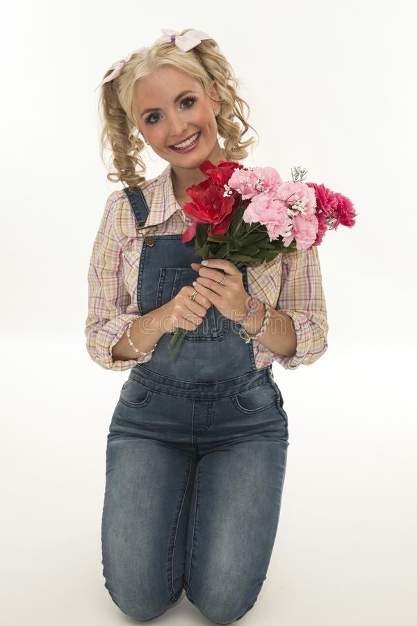 Young woman holding a bouquet of flowers. Portrait of adorable young woman holding a bouquet of flowers isolated stock images