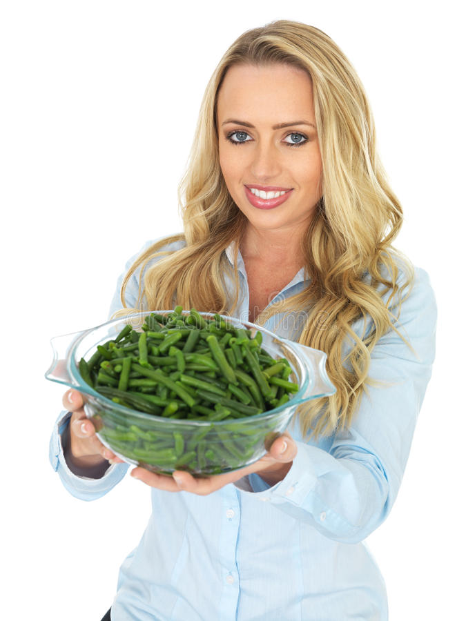 Young Woman Holding a Bowl of Cooked Green French Beans. Attractive Happy Young Woman, with long blonde hair in her twenties, holding or offering a Bowl of royalty free stock images