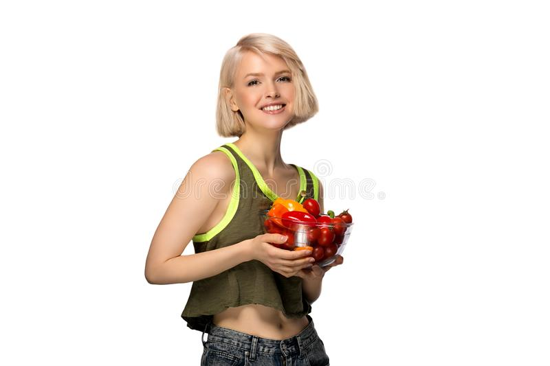 Woman with bowl of vegetables. Young woman holding bowl of vegetables pepper and tomatoes isolated on white background stock photography