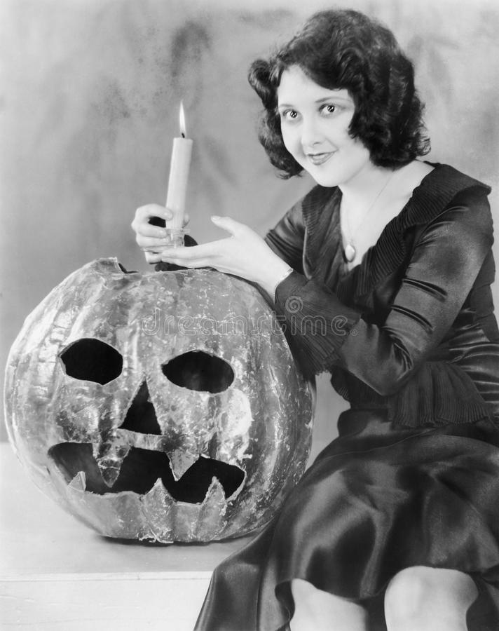 Young woman holding a burning candle on a Jack O' Lantern and smiling royalty free stock image