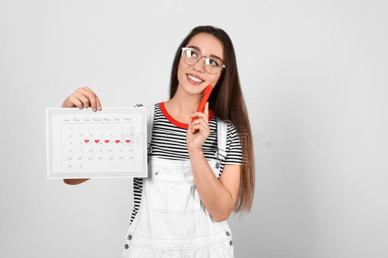 Young woman holding calendar with marked menstrual cycle days on light background stock image