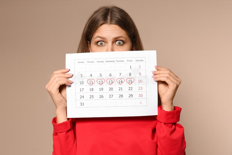 Young woman holding calendar with marked menstrual cycle days on beige background stock photography