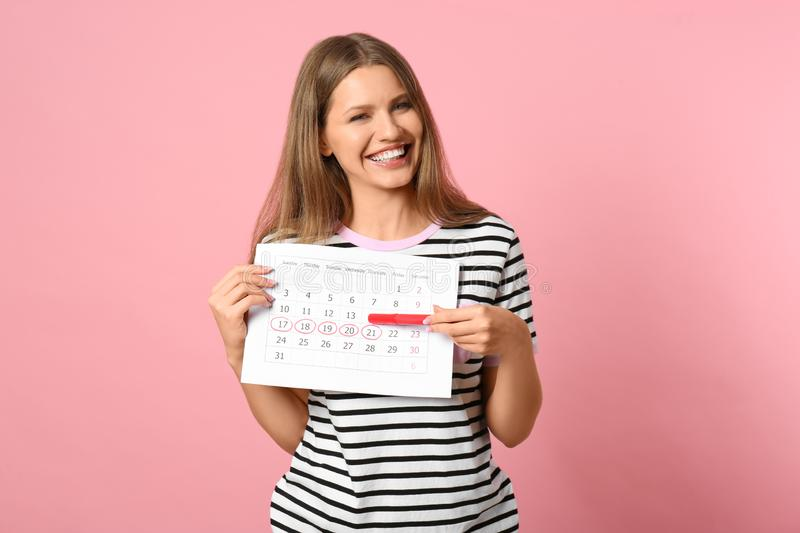 Young woman holding calendar with marked menstrual cycle days on pink background royalty free stock images