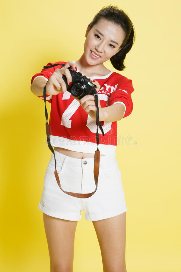 Young woman holding a camera. Isolated on background stock image
