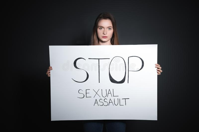 Young woman holding card with words STOP SEXUAL ASSAULT against background royalty free stock photos