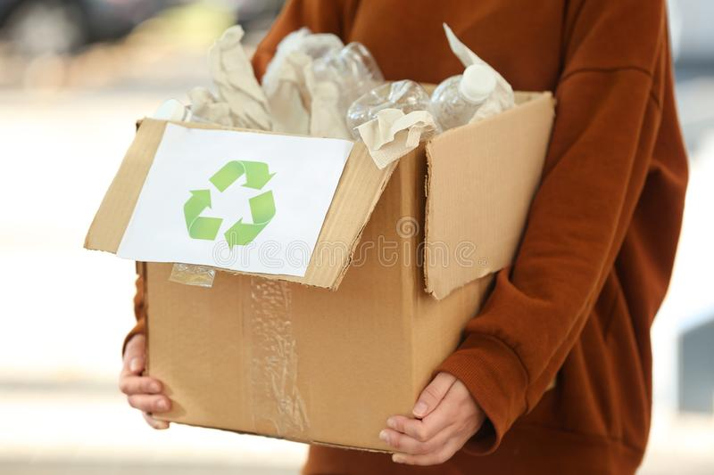 Young woman holding cardboard box with plastic bottles outdoors. Recycling concept stock photo