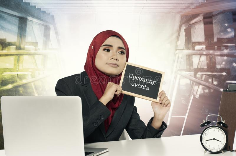 Young woman holding chalkboard with word Upcoming events over abstract background royalty free stock photography
