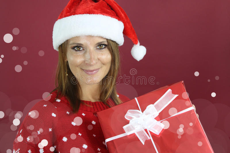 Young woman holding a Christmas present. Over a red background royalty free stock photography