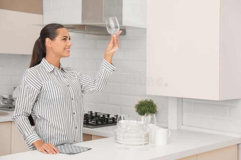 Young woman holding clean glass in kitchen. stock image