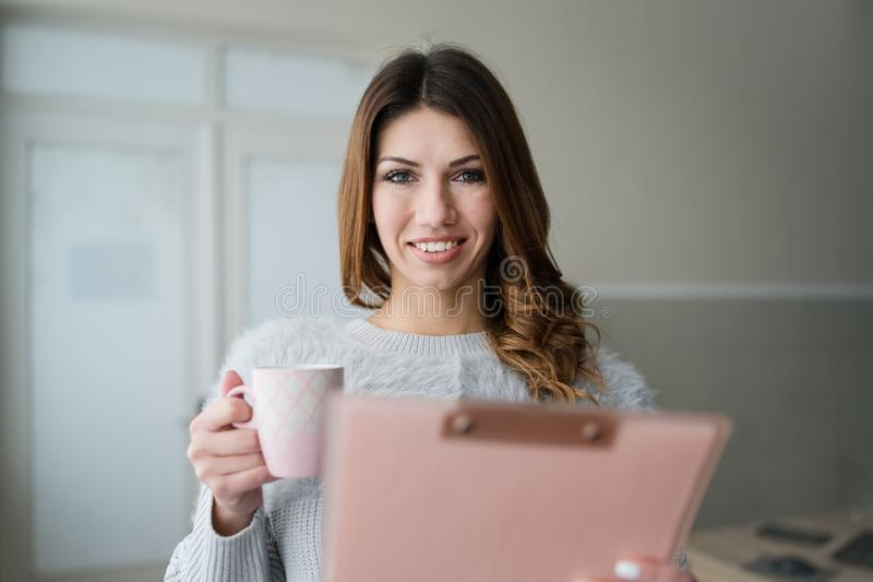 Young Woman Holding Clipboard by the Window At Work. Pretty Woman Smiling, standing by the window in the office. Secretary, holding clipboard, checking data and stock photo